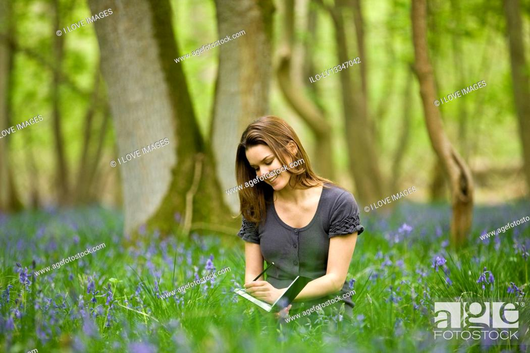 Stock Photo: A young woman sitting amongst bluebells, drawing.