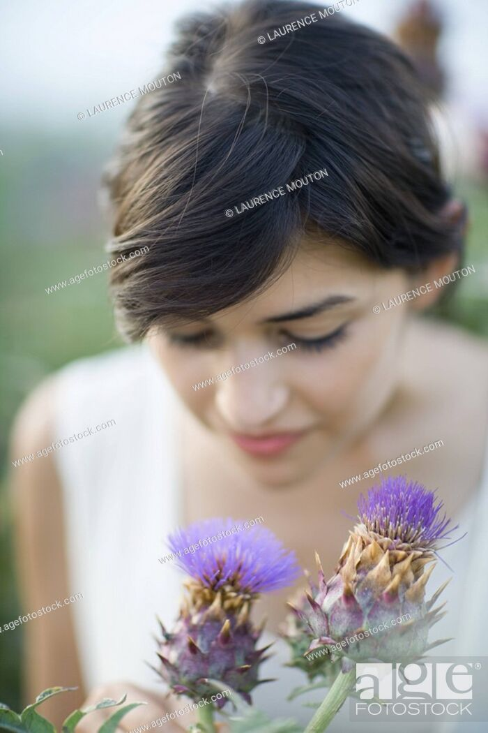 Stock Photo: Young woman smelling thistle flowers.