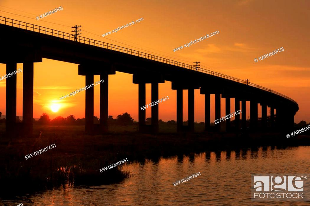 Stock Photo: A train bridge at Pa Sak Jolasid Dam, Thailand in sunset time.