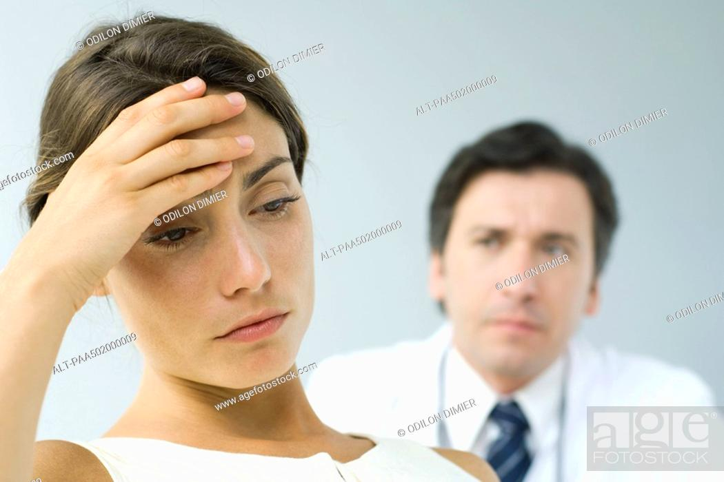 Stock Photo: Woman holding head, looking down, doctor in background.