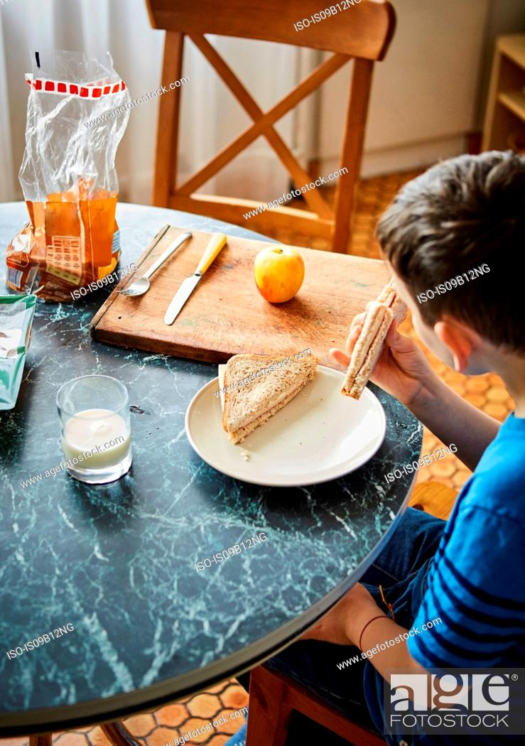 Stock Photo: Boy at dining table eating sandwich.