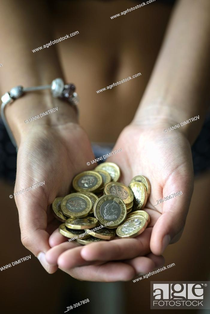Imagen: Hands full with UK Pound Coins.