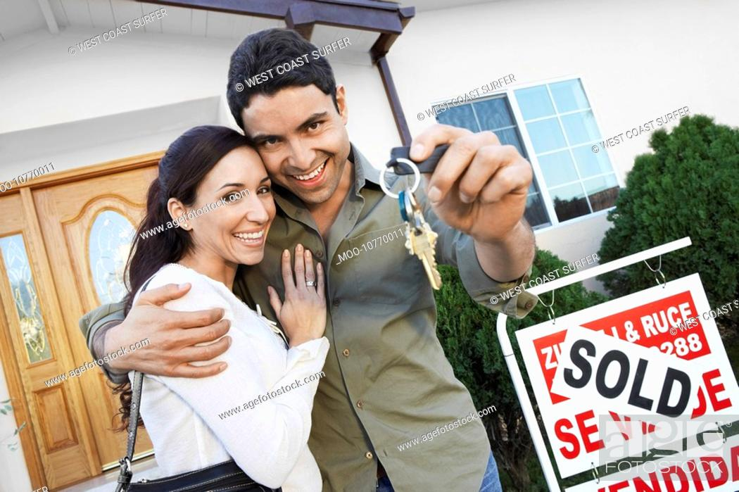 Stock Photo: Homeowners standing in front of house with Sold sign holding key portrait.