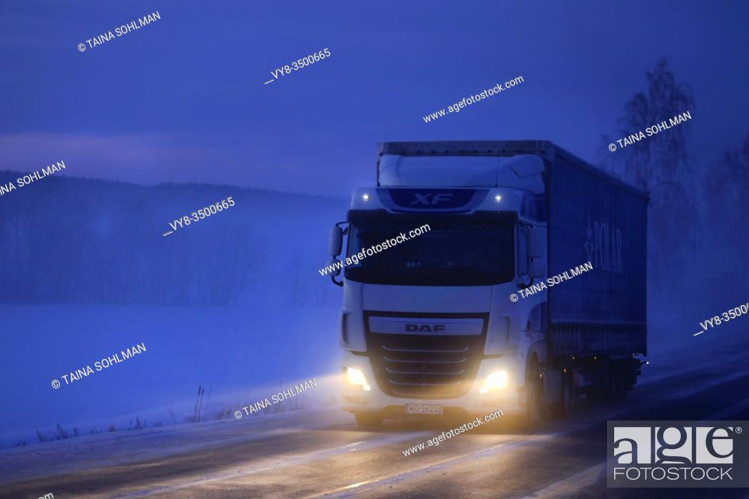 Stock Photo: White DAF XF truck pulls semi trailer on icy road on a foggy winter evening at twilight in South of Finland. Salo, Finland. January 18, 2019.