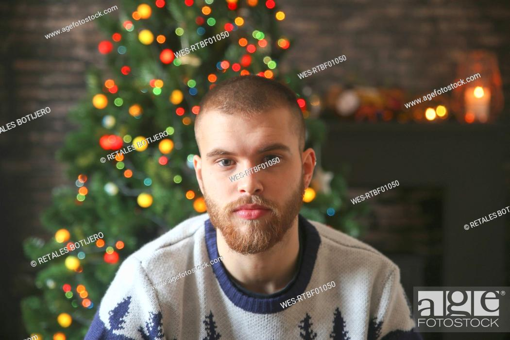 Stock Photo: Portrait of serious young man with full beard in front of lighted Christmas tree at home.
