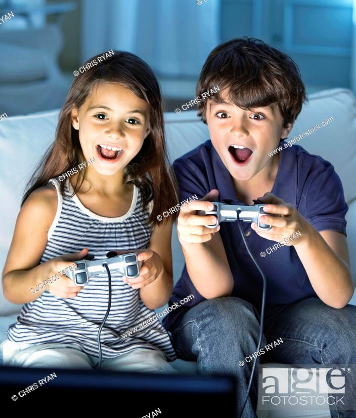 Stock Photo: Brother and sister playing video games in living room.