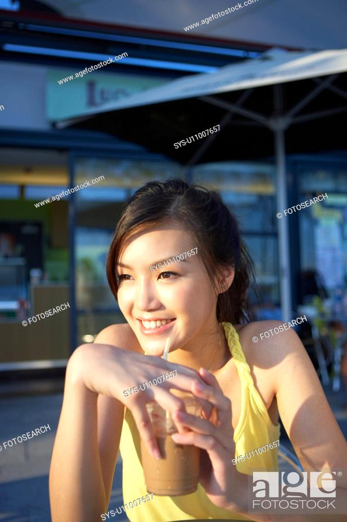 Stock Photo: Young Lady Sitting at Outdoor Cafe, Holding Cold Drink, Looking Away.