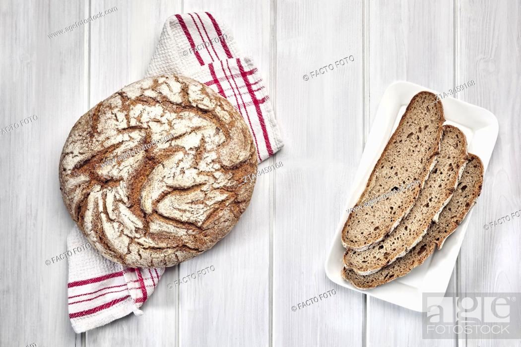 Imagen: Loaf of rye bread and three slices on a white wooden background.