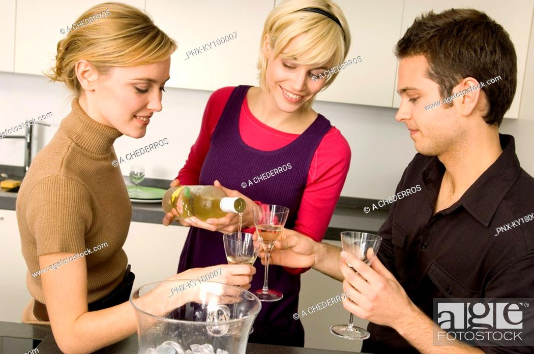 Stock Photo: Young woman pouring wine for her friends.
