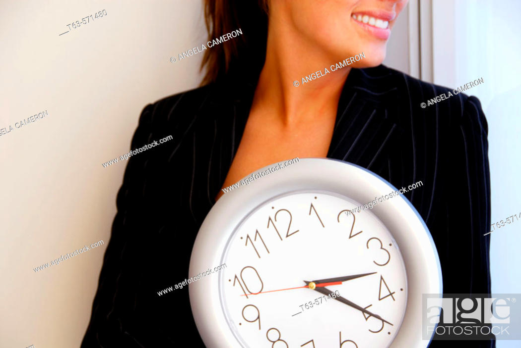 Stock Photo: 20 yr old young woman holding clock in office.