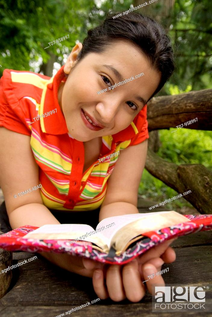Stock Photo: Latino woman reading book.