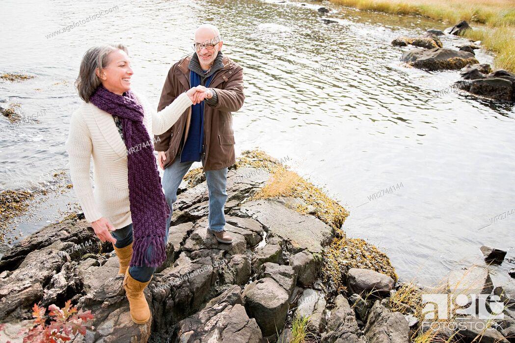 Stock Photo: Mature couple walking over rocks.