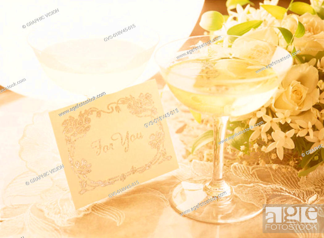 Stock Photo: Close Up of Wineglass and Bouquet of Flowers.