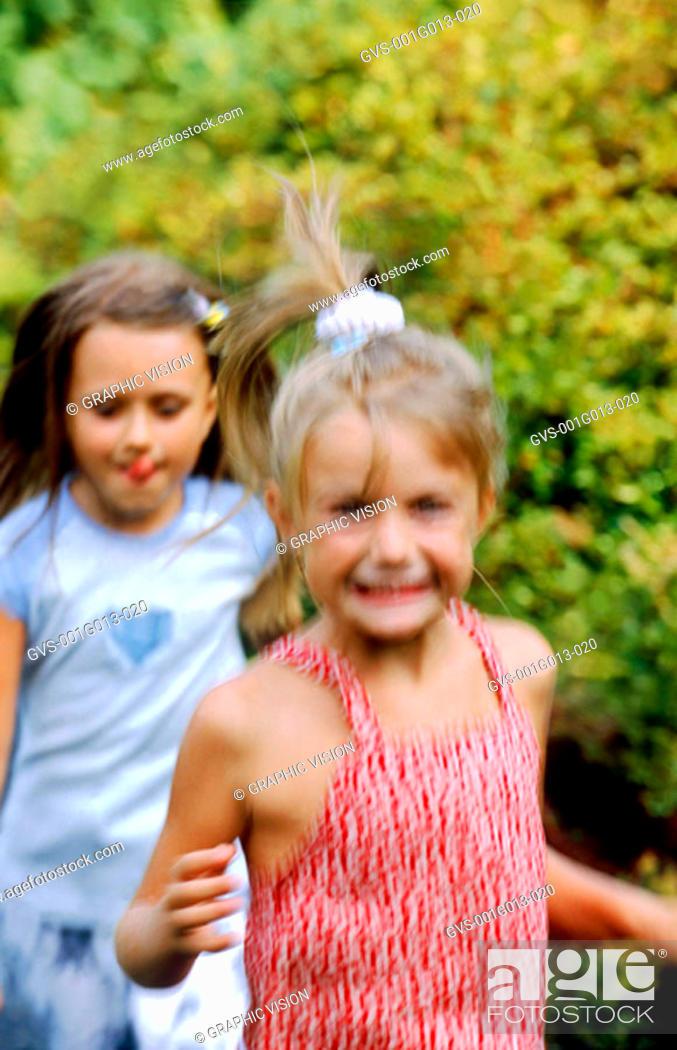 Stock Photo: Two girls running outdoors (blurred).