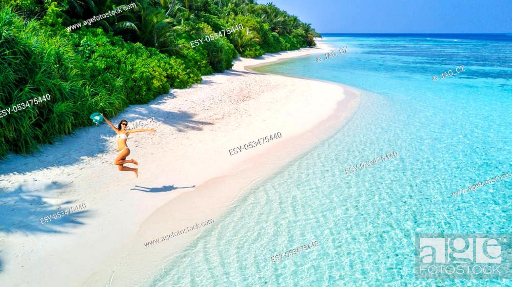 Stock Photo: Beautiful young woman jumping on tropical beach on Maldives. Concept of freedom, vacation, travel and beach holidays. Summer theme.