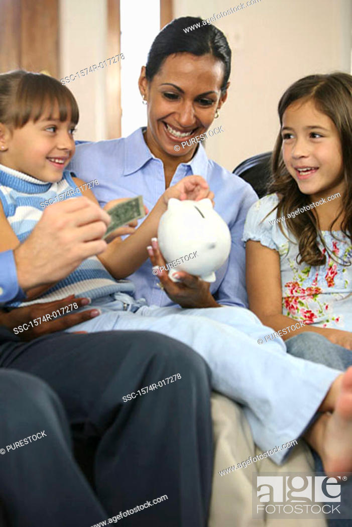 Stock Photo: Parents sitting with their two daughters smiling.