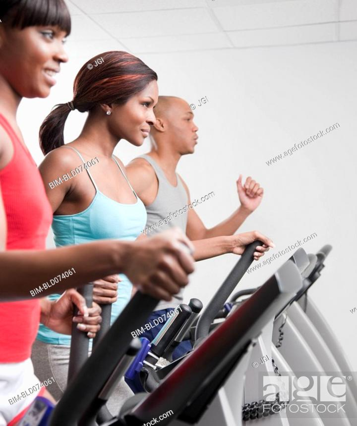 Stock Photo: African people using exercise equipment in health club.