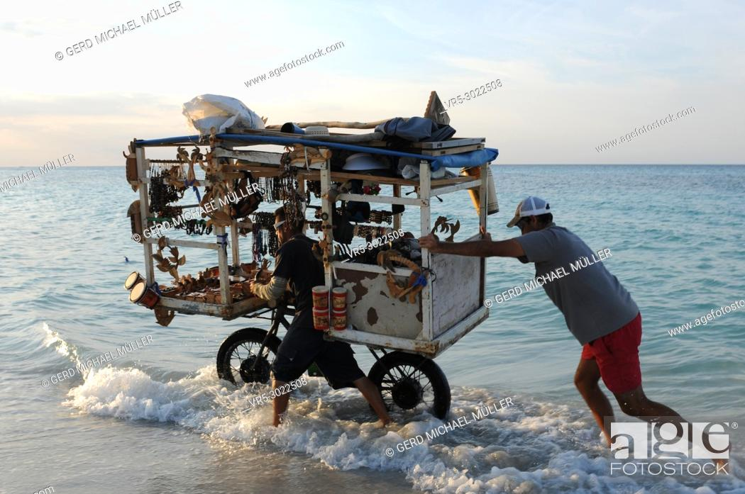 Stock Photo: Cuba: Beach souvenier trader pushing his heavy loaded bicycle trought the water at Varadero beach.