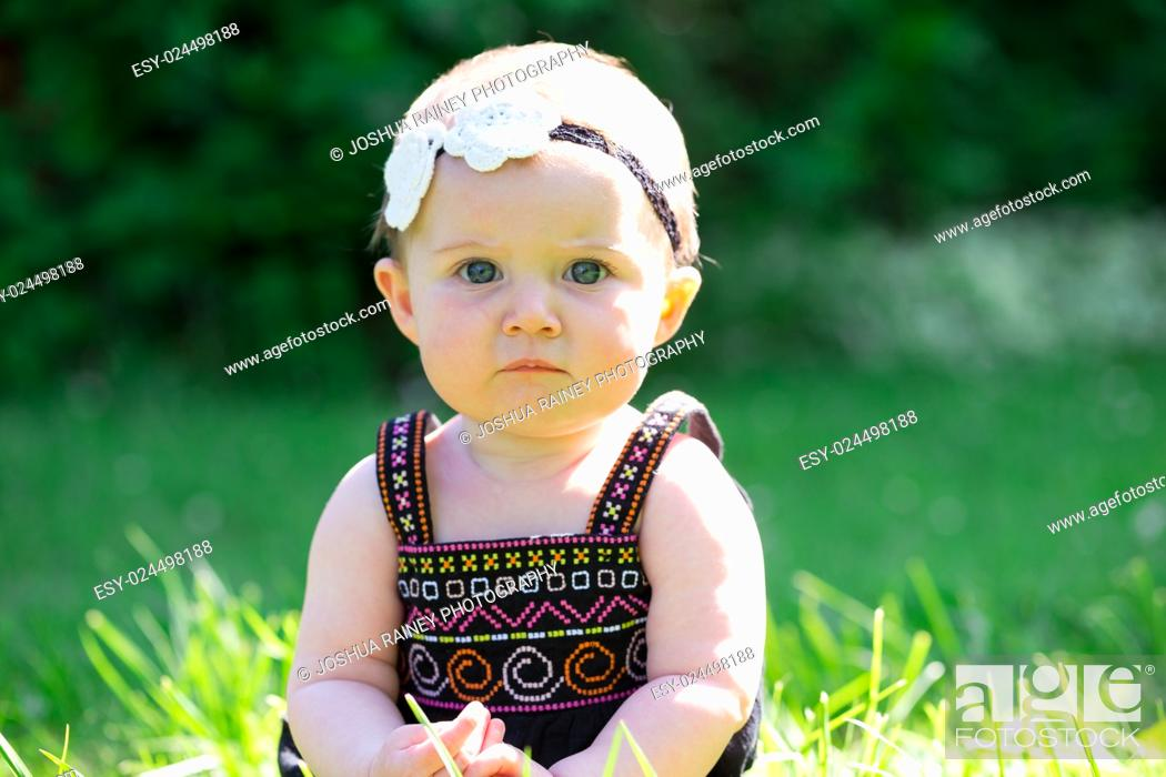 Stock Photo: Baby girl at roughly 6 months old outdoors in a natural setting with available light for a lifestyle portrait.