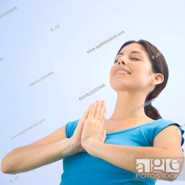 Stock Photo: Low angle view of Hispanic woman praying.