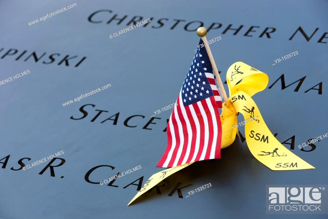 Stock Photo: A small American flag and a yellow ribbon left on the names inscribed in the perimeter of one of the pools at the National September 11 Memorial in New York.