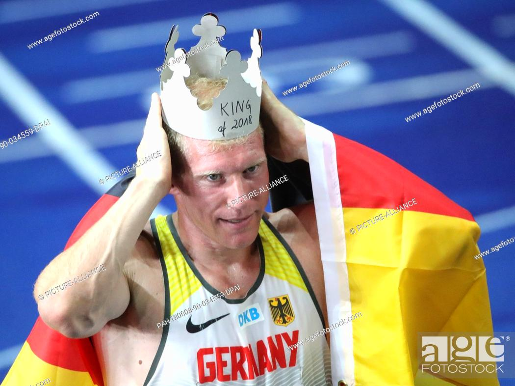 Stock Photo: 08.08.2018, Berlin: Athletics, European Championships in the Olympic Stadium: Decathlon, 1500 m, Men, Arthur Abele from Germany celebrates gold and puts on a.