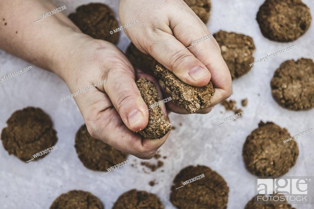 Photo de stock: High angle close up of person breaking freshly baked chocolate cookie in half.