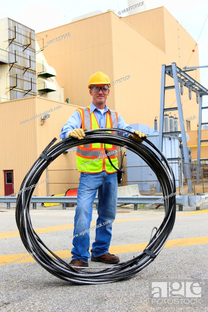 Stock Photo: Engineer at electric power plant carrying coil of wire at storage area.