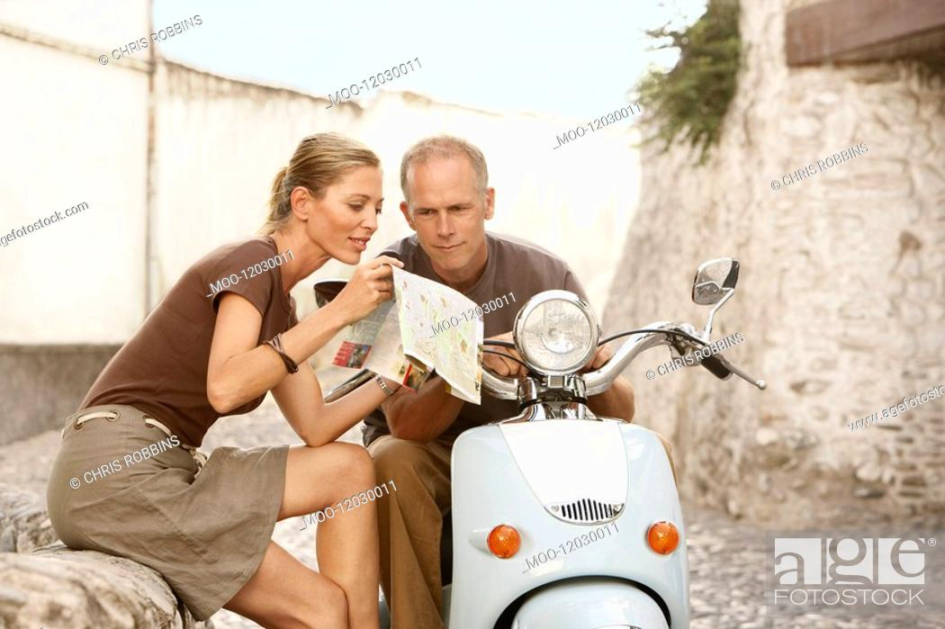 Stock Photo: Couple With Scooter Reading Map on old street in Granada Spain.