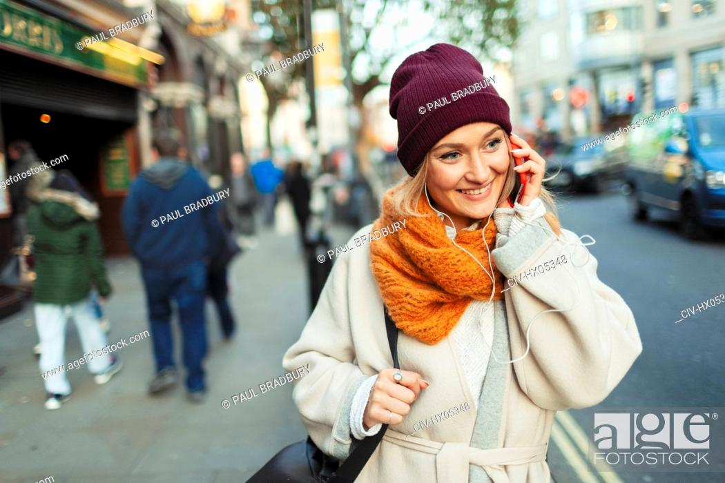 Imagen: Young woman in stocking cap and scarf talking on smart phone on urban sidewalk.