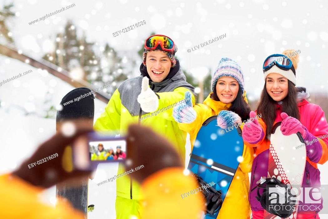 Stock Photo: winter sport, technology, leisure, friendship and people concept - happy friends with snowboards and smartphone taking picture outdoors.