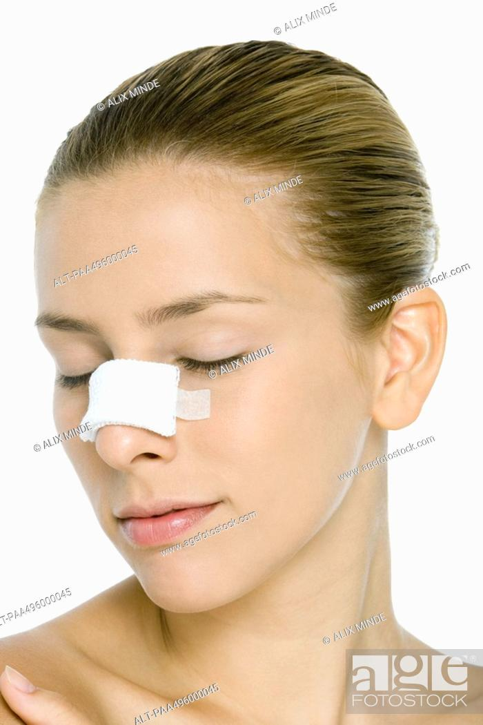 Stock Photo: Young woman with bandaged nose, eyes closed.