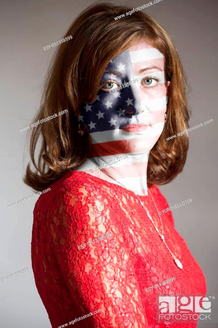 Imagen: Portrait of woman with painted USA flag on a gray background.