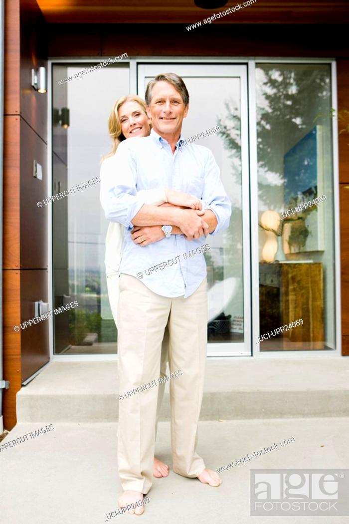 Stock Photo: Portrait of barefoot couple hugging on front stoop.