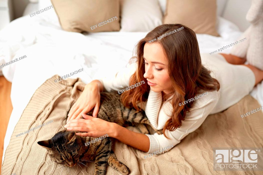 Stock Photo: pets, comfort, rest and people concept - happy young woman with cat lying in bed at home.