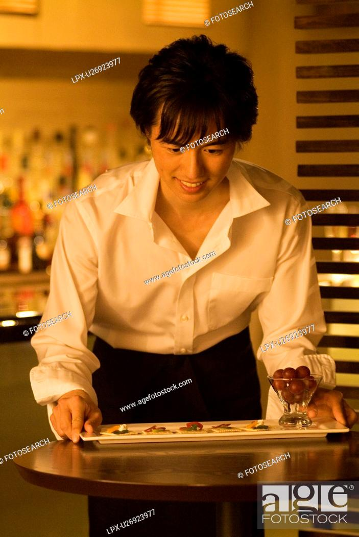 Stock Photo: Waiter carrying a plate of food to a table.