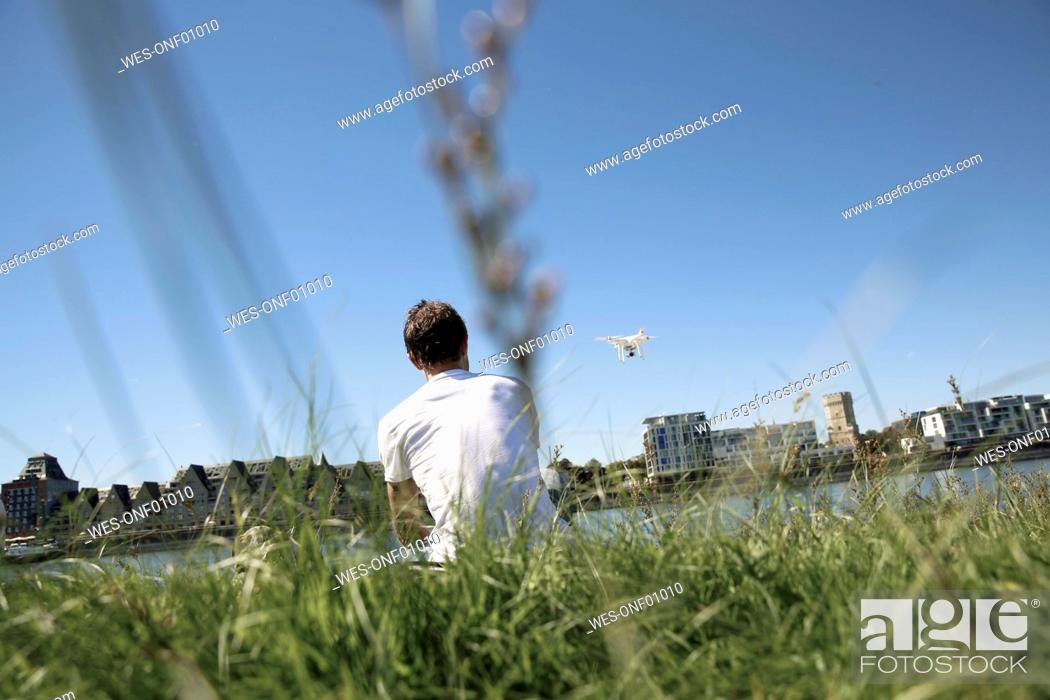 Stock Photo: Mature man sitting in grass flying a drone.