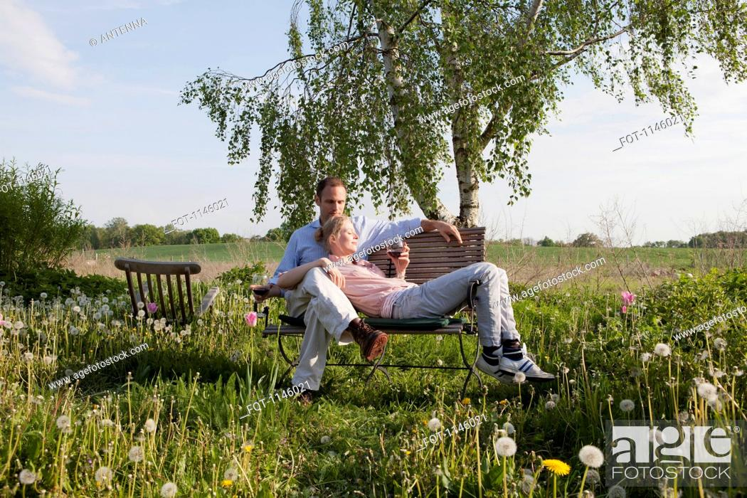 Stock Photo: A couple enjoying sunshine and wine on a bench in their backyard.