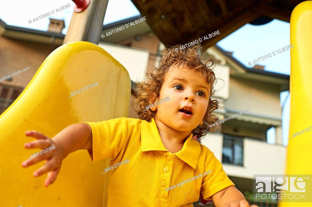 Stock Photo: A twenty months old caucasian girl playing on a slide.