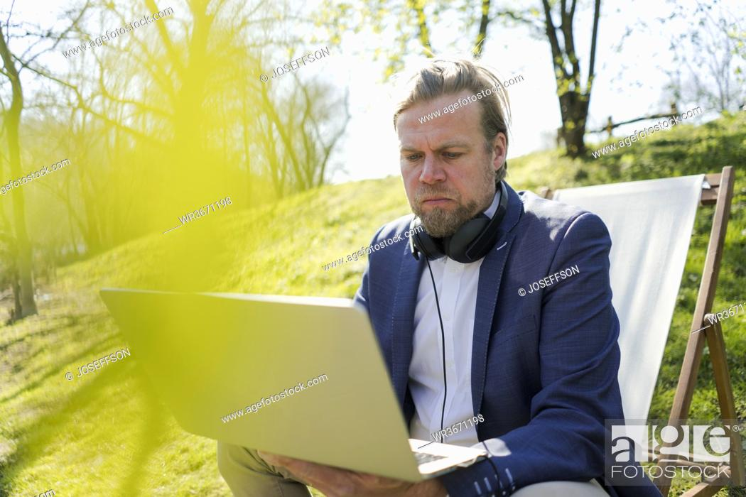 Stock Photo: Mature male entrepreneur using laptop while sitting on chair at park during summer.