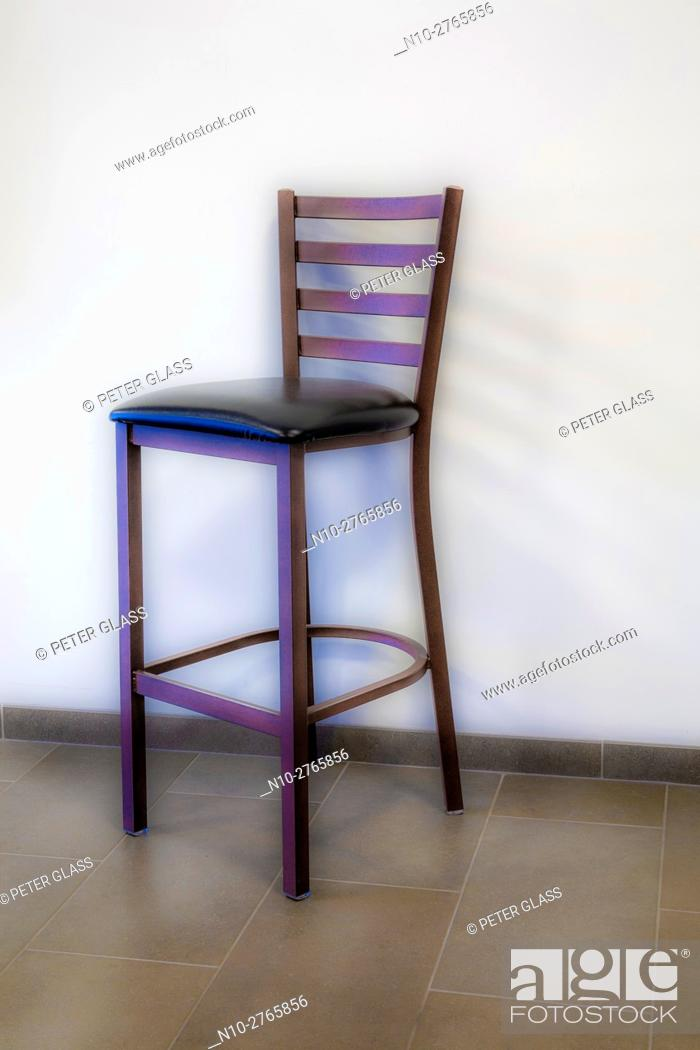 Stock Photo: Bar chair by a wall.