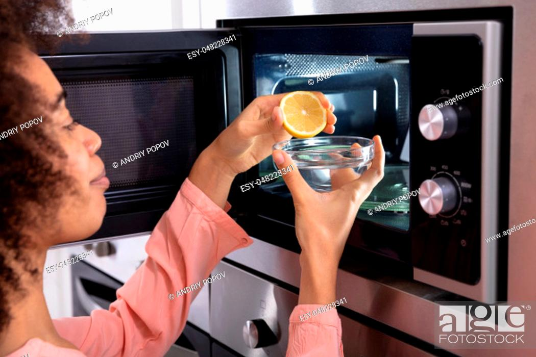 Stock Photo: Woman's Hand Squeezing Halved Lemon In The Glass Bowl Near An Open Microwave Oven.