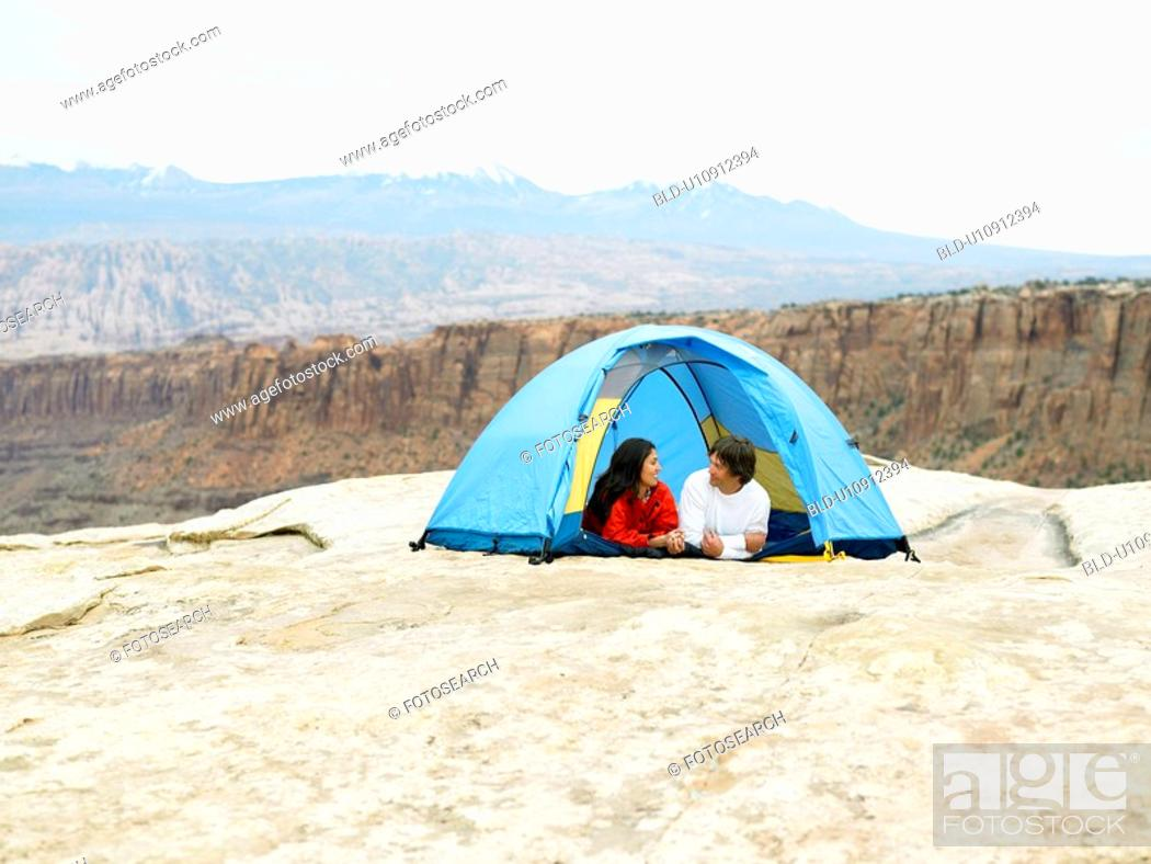 Stock Photo: Couple in tent, rock strata in background, Moab, Utah, USA.