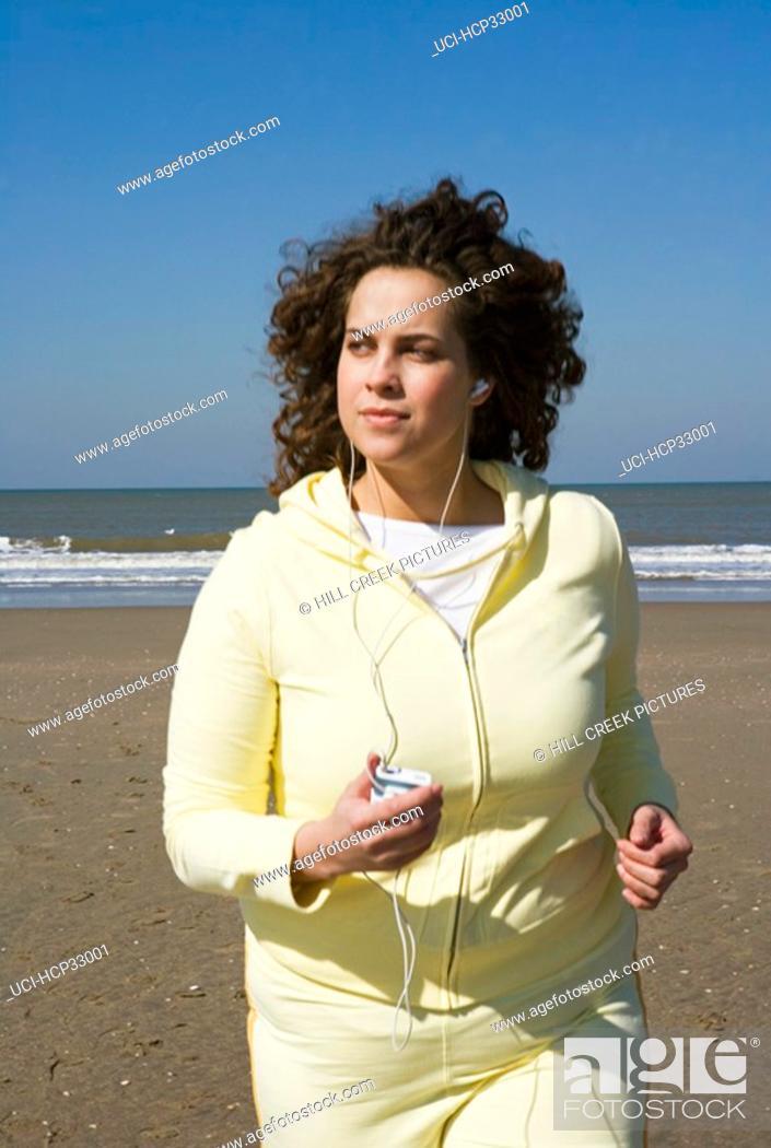 Stock Photo: Woman listening to music, jogging on beach.