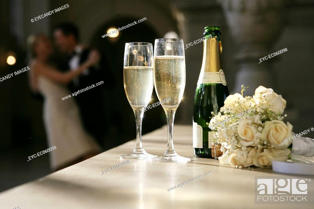 Stock Photo: Couple in background of a bottle of champagne.