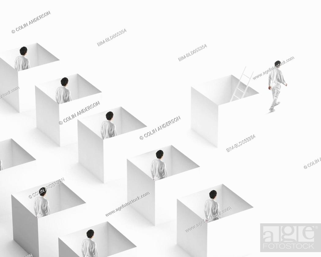 Stock Photo: European businessman walking away from businessmen in boxes.