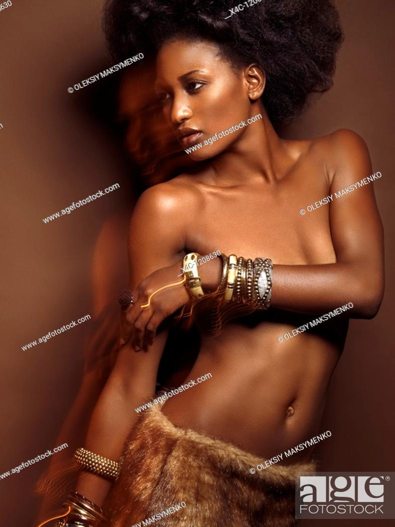 Stock Photo: High fashion photo of a young beautiful woman wearing jewelry posing on brown background.