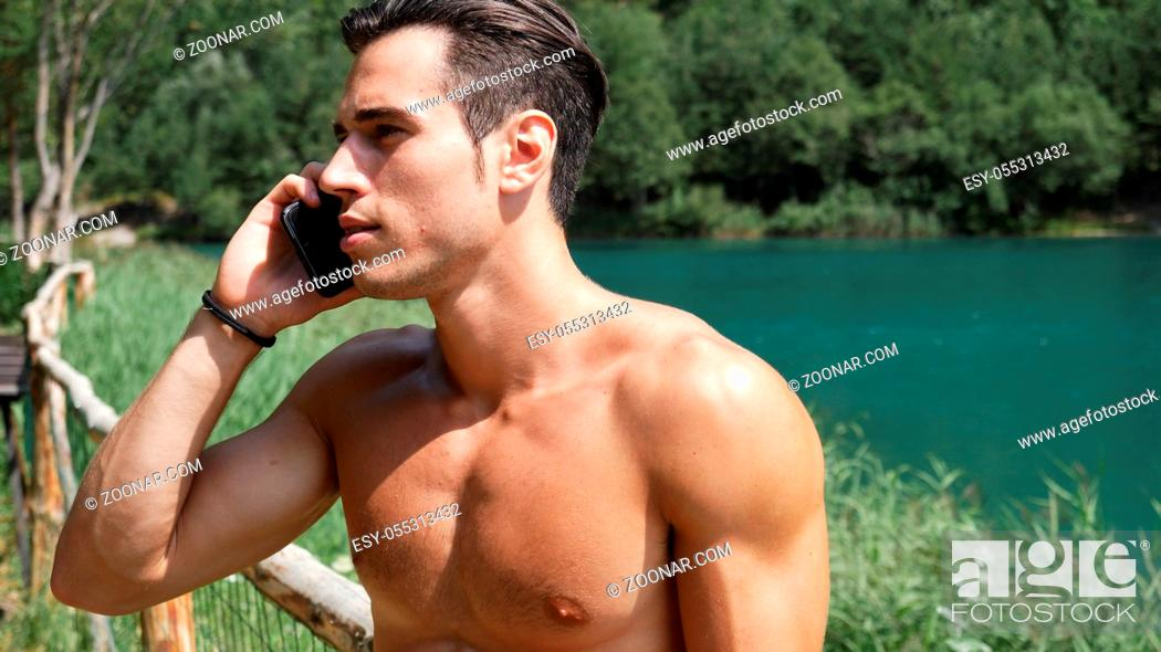 Photo de stock: Young shirtless muscular handsome man making a phone call with smartphone at lake in forest, talking to someone.