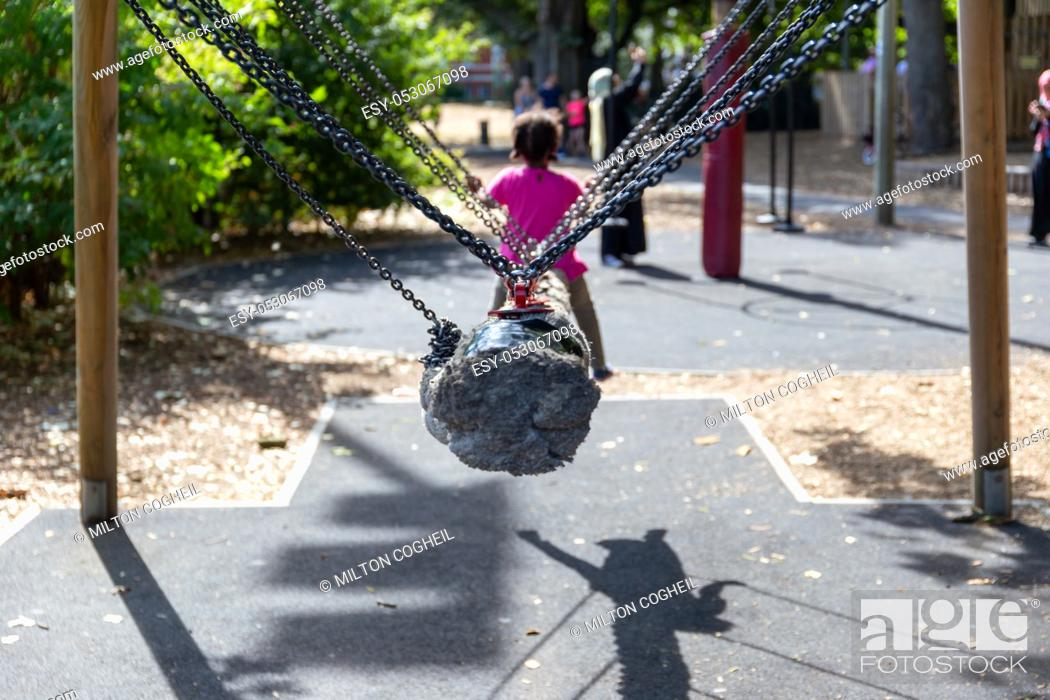 Stock Photo: Child riding a rope snake swing in the playground at Battersea Park, London, UK.