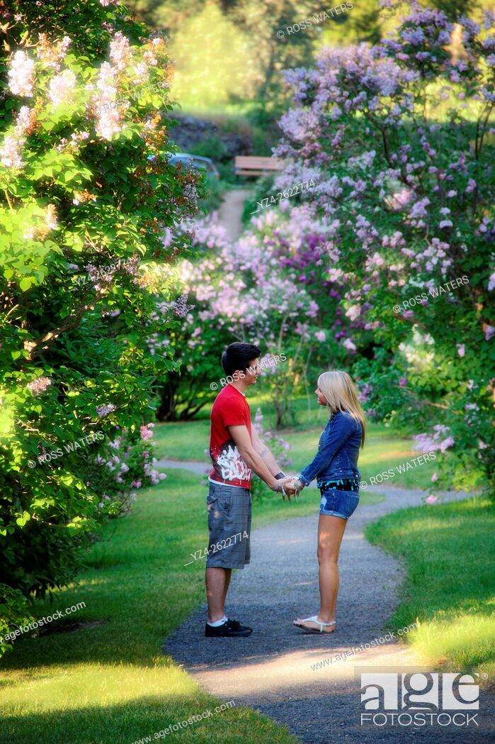 Photo de stock: A young couple together outdoors in a lilac garden.